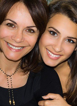 A mom and daughter with beautiful smiles