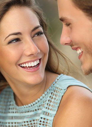 Woman with white teeth smiling at a man