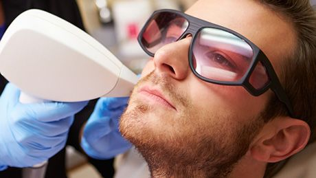 Man wearing protective eyewear while receiving laser treatment
