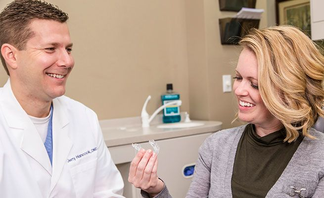 Dr. Hancock showing a patient an Invisalign® tray
