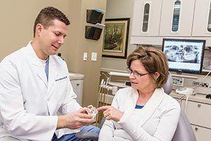 Dr. Hancock showing a patient a dental appliance
