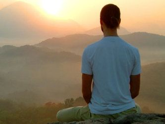 Man mediating at top of mountain