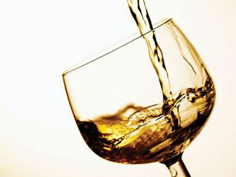 Wine glass being filled with white wine
