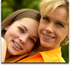 Smiling mother hugging daughter with braces