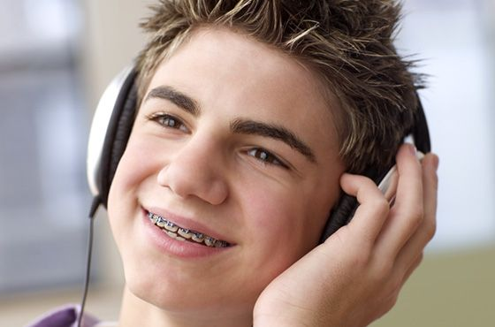 Smiling teenage boy with braces listening to headphones