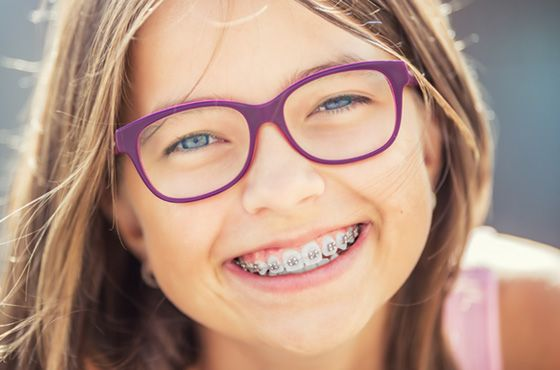 Young smiling girl with braces and glasses