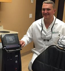 Dr. Aldredge with dental laser machine