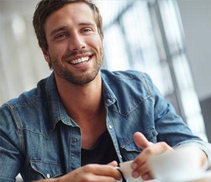 Image of smiling man in denim shirt