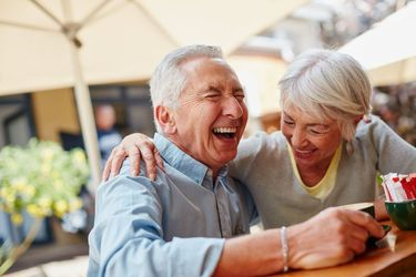 An older couple smiles and laughs