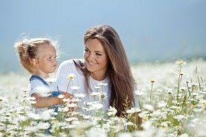 Mom in field of flowers with young girl
