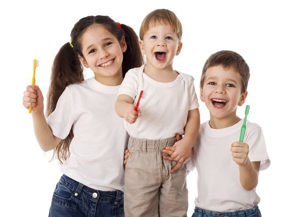 Three smiling children holding toothbrushes