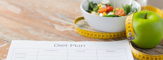 Photo of a paper for a diet plan with an apple and a bowl of salad