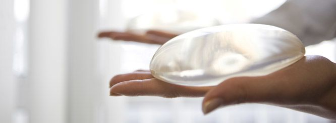 Photo of hands holding breast implants