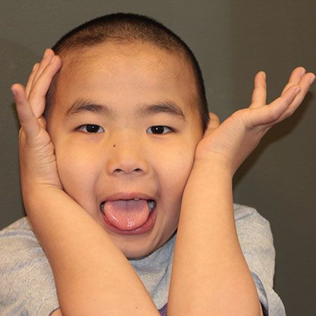 Asian boy making silly face for photo