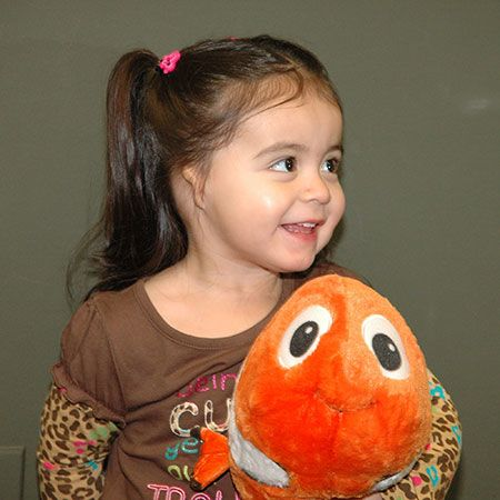 Cute little girl with misshapen ear holding fish plush