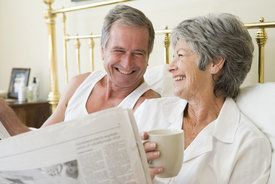 Couple reading newspaper and laughing in bed