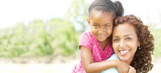 Smiling mom piggybacking daughter