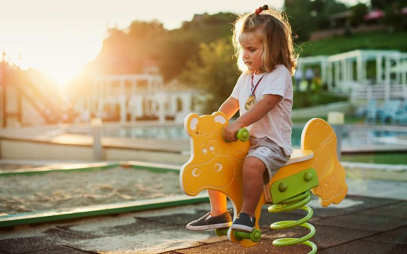 A young child sits unsupervised on a toy horse in a playground