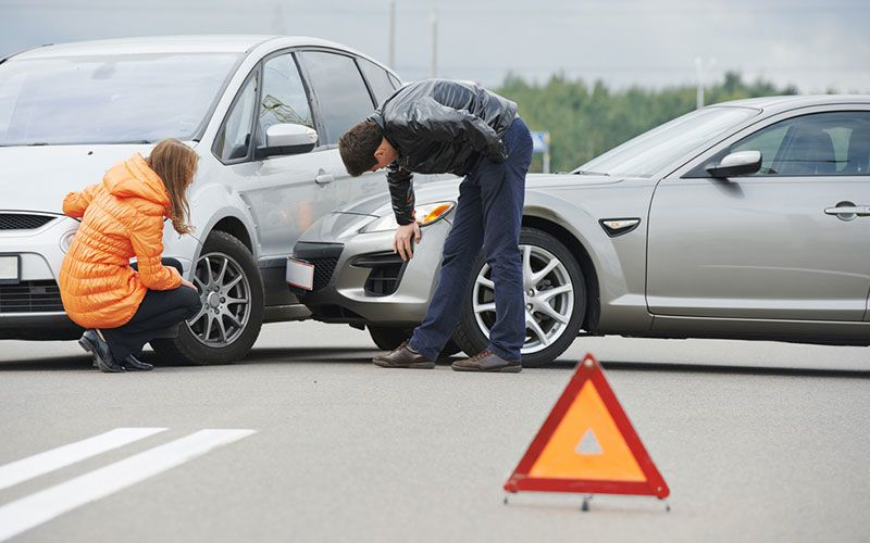 Photo of two people examining cars after a collision