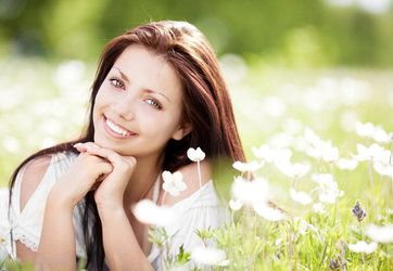 A young woman smiles among wildflowers