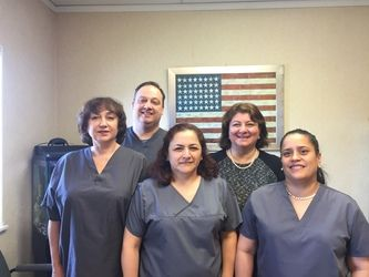 A group photo of the five-member team providing patients at Dental Health Paltac and Associates with dental care
