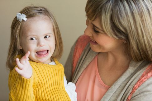 Photo of woman holding child with Downs syndrome