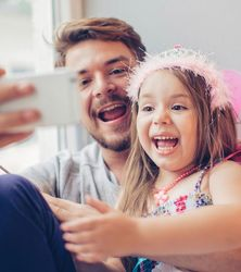 Dad laughing and taking selfie with young daughter