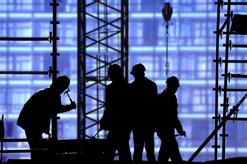 A silhouette of a group of men working on a construction site