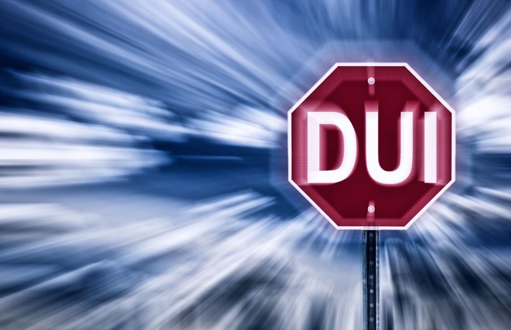 A stop sign is blurry and reads dui instead of stop
