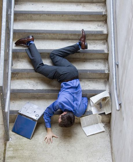 A business man lays on a set of stairs after a slip and fall