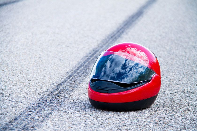 A motorcyclist helmet lays next to a skidmark on a road after an accident
