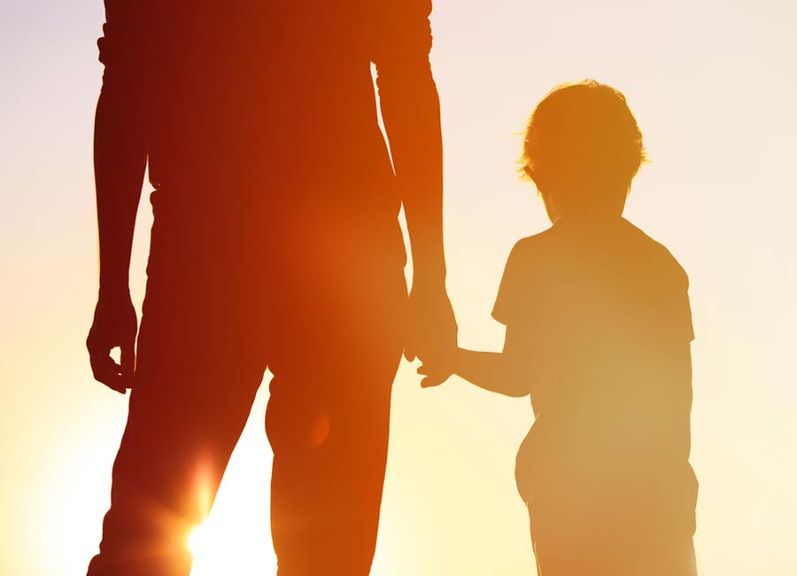 an adult holding hand with a child at sunset