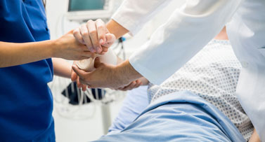 Patient holding medical personnel's hands