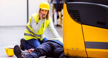 Construction worker on phone over injured coworker