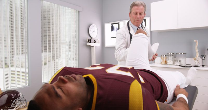A football player lies on a doctor's table