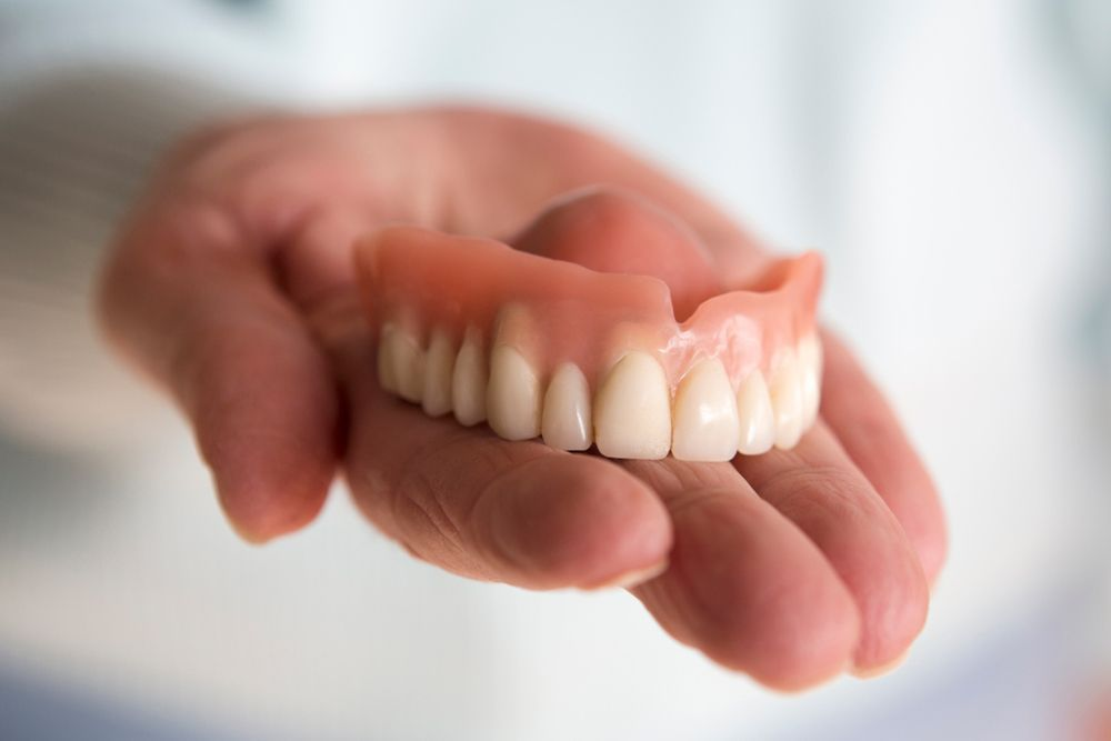 A hand holding a set of traditional dentures