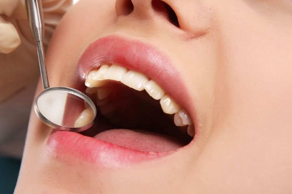 A woman's mouth and a dental mirror