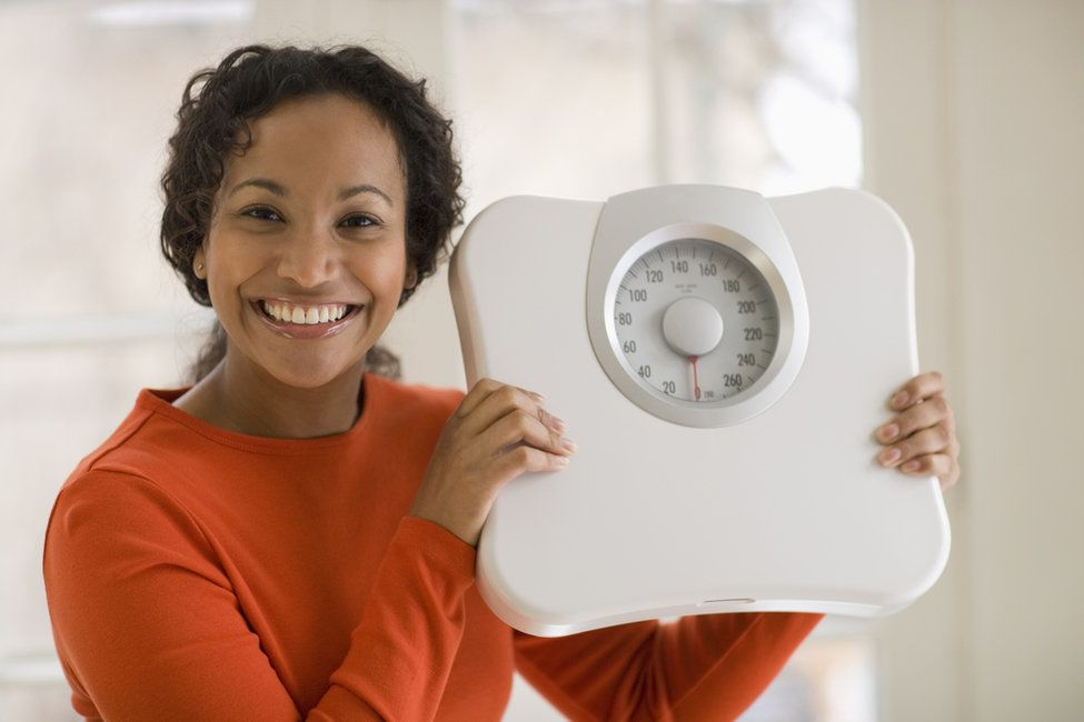 Photo of a woman holding a scale