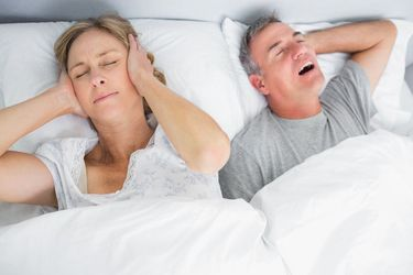 A woman covers her ears while her partner snores loudly