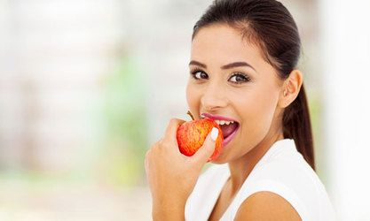 Beautiful woman with ponytail eating apple