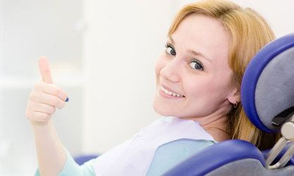 Woman sitting in dentist chair and giving thumbs up