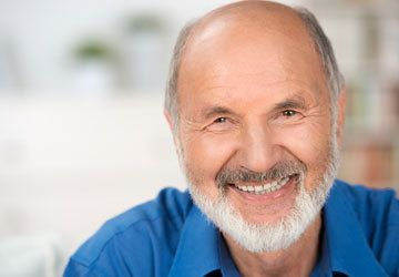 Bald white man smiling with blurry background