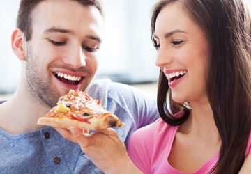 Woman laughing and putting pizza in man's mouth
