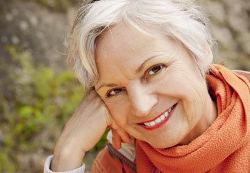 Older white woman smiling with orange scarf