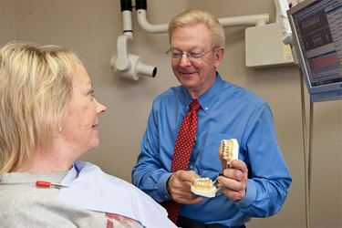 Dr. Korn showing a model of a mouth to a patient