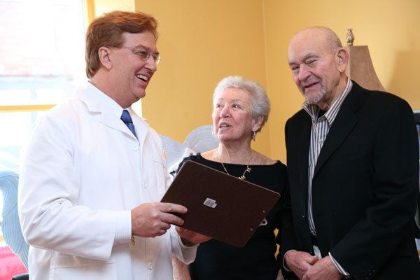 Dr. Regni laughing with dentures patient