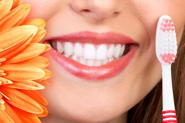 Smiling woman's mouth next to flower and toothbrush