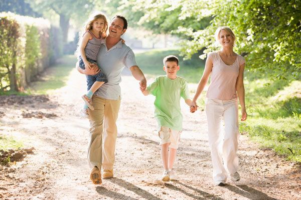 Smiling family walking on sunny path