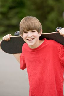 Smiling boy with skateboard over shoulders