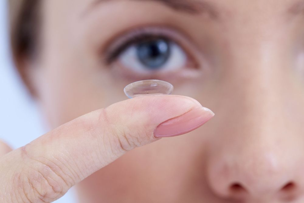 Photo of a woman holding a contact lens